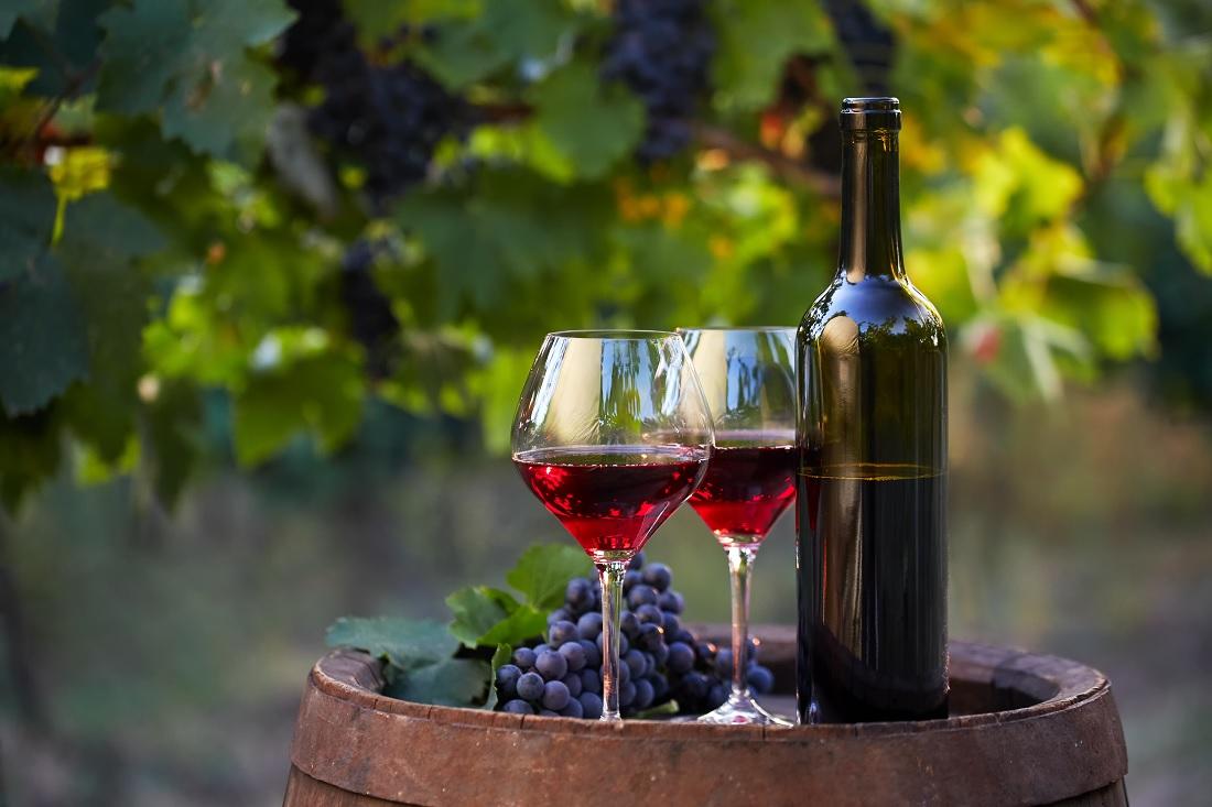 ブドウの樹の前の樽に置かれた赤ワインが入ったグラスとボトル