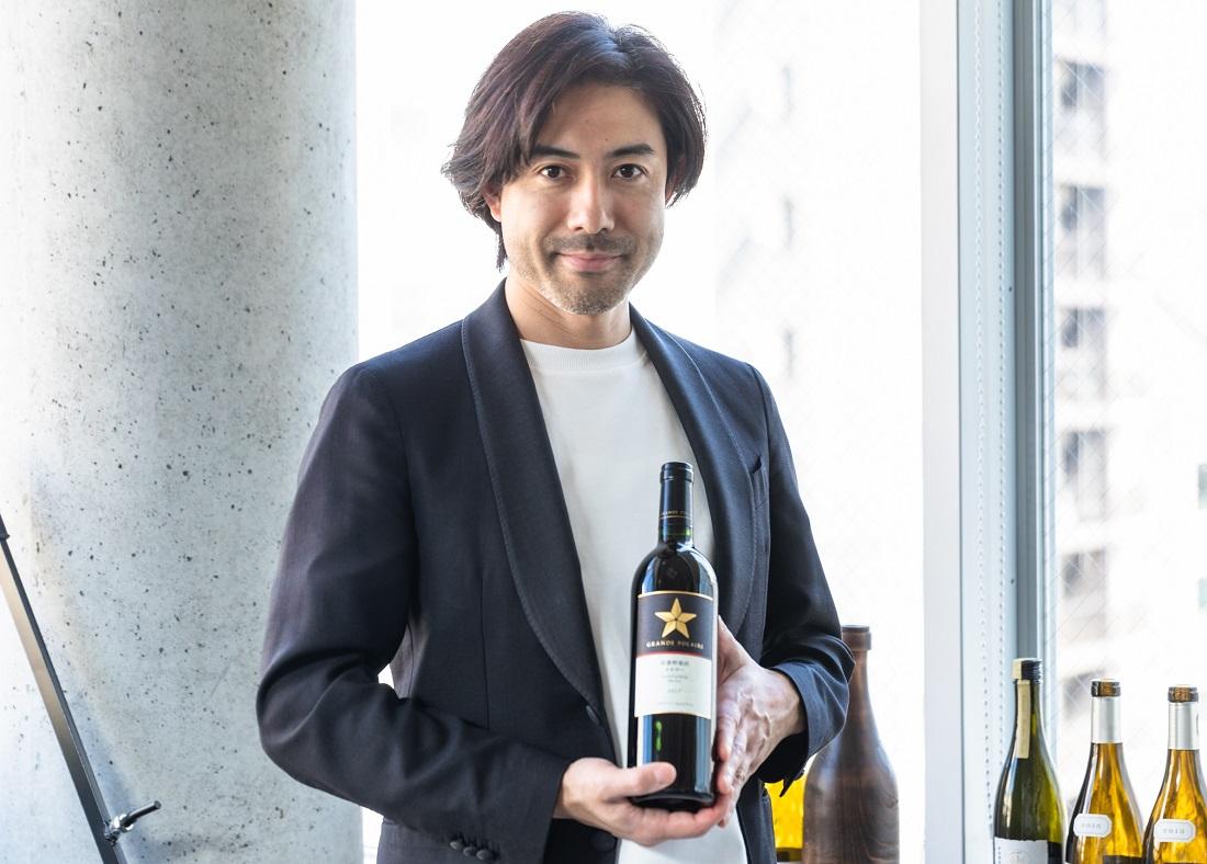 グランポレール 安曇野池田シリーズのワインボトルを手にするグランポレールのアンバサダー大越基裕さん