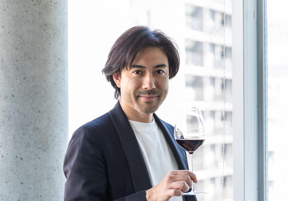 窓辺でワイングラスを片手にするグランポレールのアンバサダー大越基裕さん