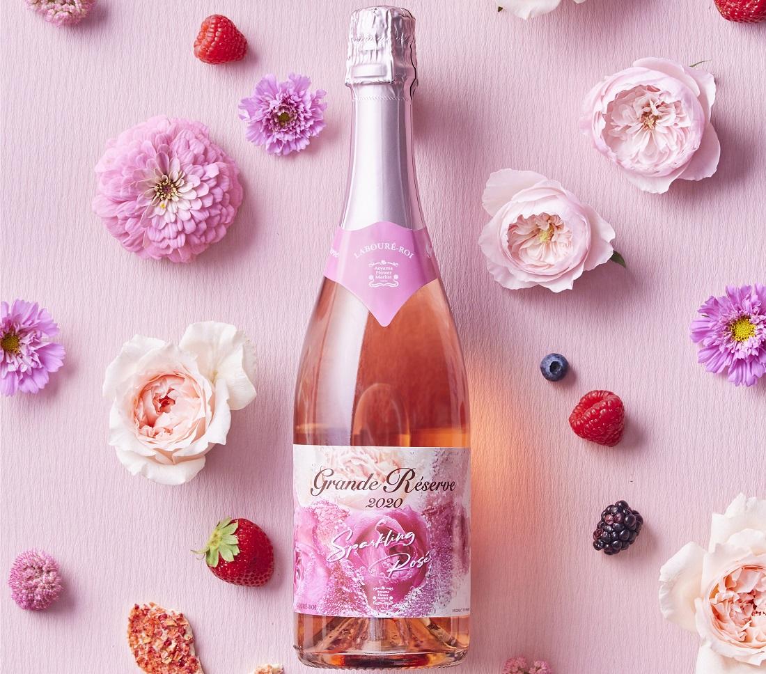 ピンクを背景にしたバラやフルーツとグランド・レゼルヴ スパークリング ロゼ 2020のワインボトル