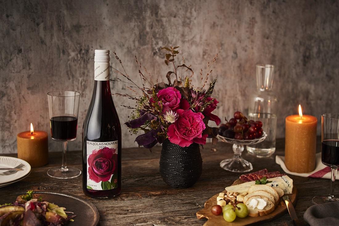 バラの花束とともに食卓で楽しまれるラブレ・ロワ ボージョレ・ヌーボー 2020のワインボトル