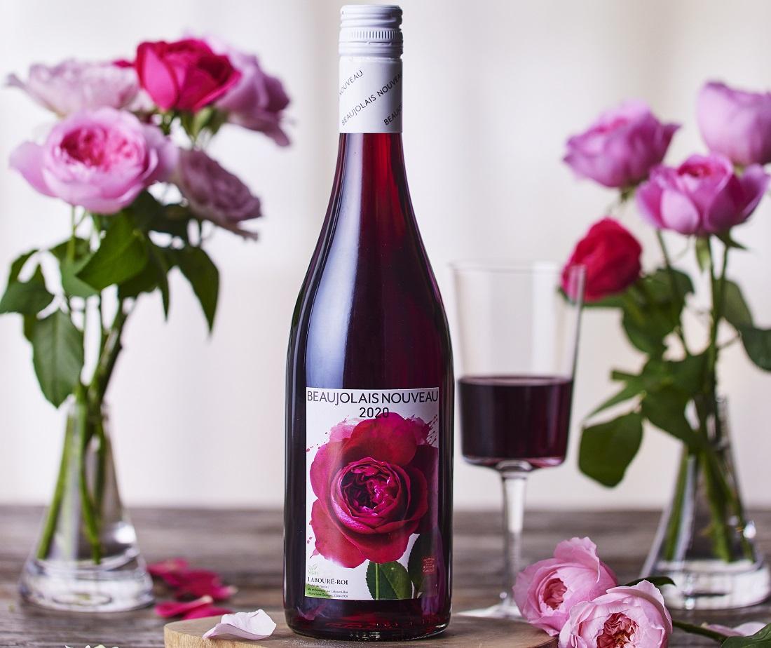 食卓に置かれたラブレ・ロワ ボージョレ・ヌーボー 2020のワインボトルとバラ
