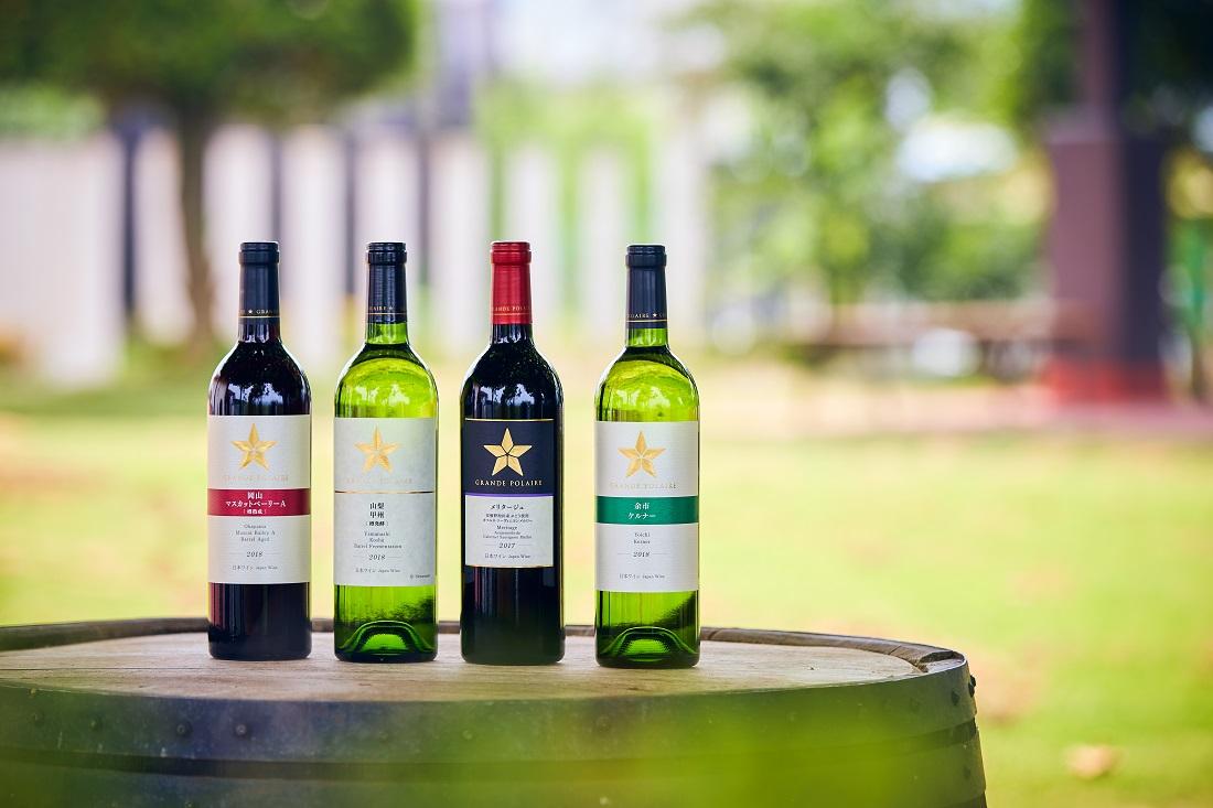 緑を背景に樽の上に4つ並んだグランポレールのワインボトル