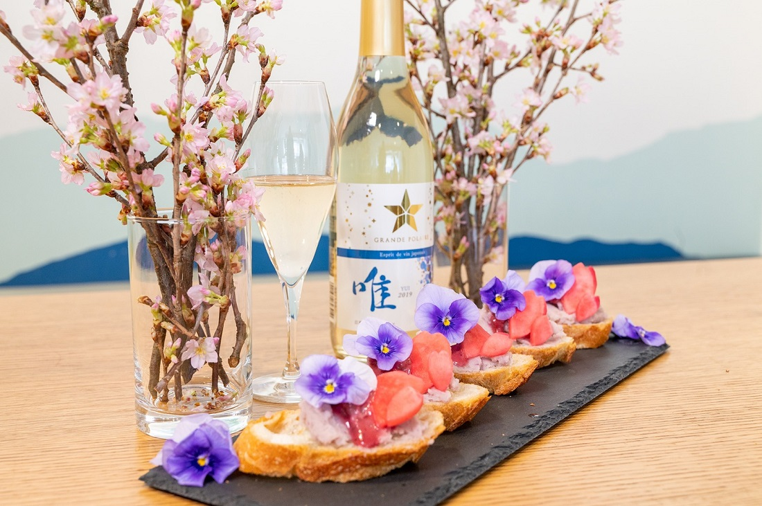 桜の花の枝を飾った食卓に並ぶ「グランポレール エスプリ ド ヴァン ジャポネ 唯 -YUI- スパークリング」ワインボトルとグラスと「ピンクポテトサラダ」