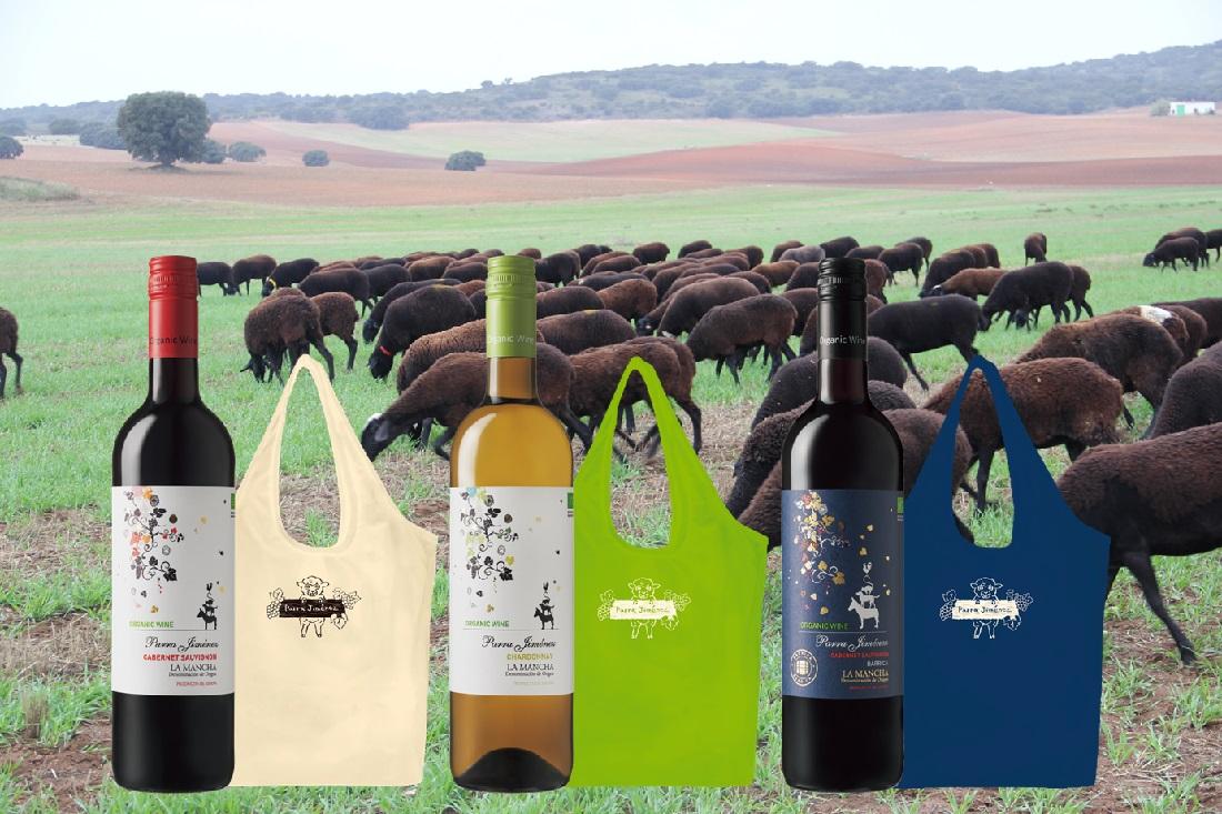 パラ・ヒメネスのワイナリー敷地内で雑草を食べる羊を背景に並ぶワインボトル3本と期間限定エコバッグ3種