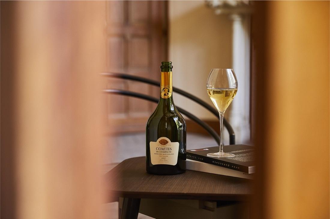 少し開いた扉の奥にあるテーブルに置かれたテタンジェ「コント・ド・シャンパーニュ ブラン・ド・ブラン」シャンパーニュボトルとシャンパーニュグラス