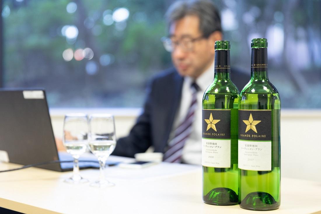チーフワインメーカー工藤を背景に立つグランポレール 安曇野池田 ソーヴィニヨンブラン ワインボトル2本
