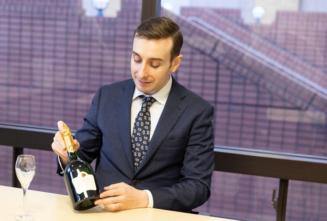 「コント・ド・シャンパーニュ ブラン・ド・ブラン 2008」のボトルを持ちながら魅力を語るテタンジェ・オフィシャル・アンバサダーのシュビヤー・クリストファー氏