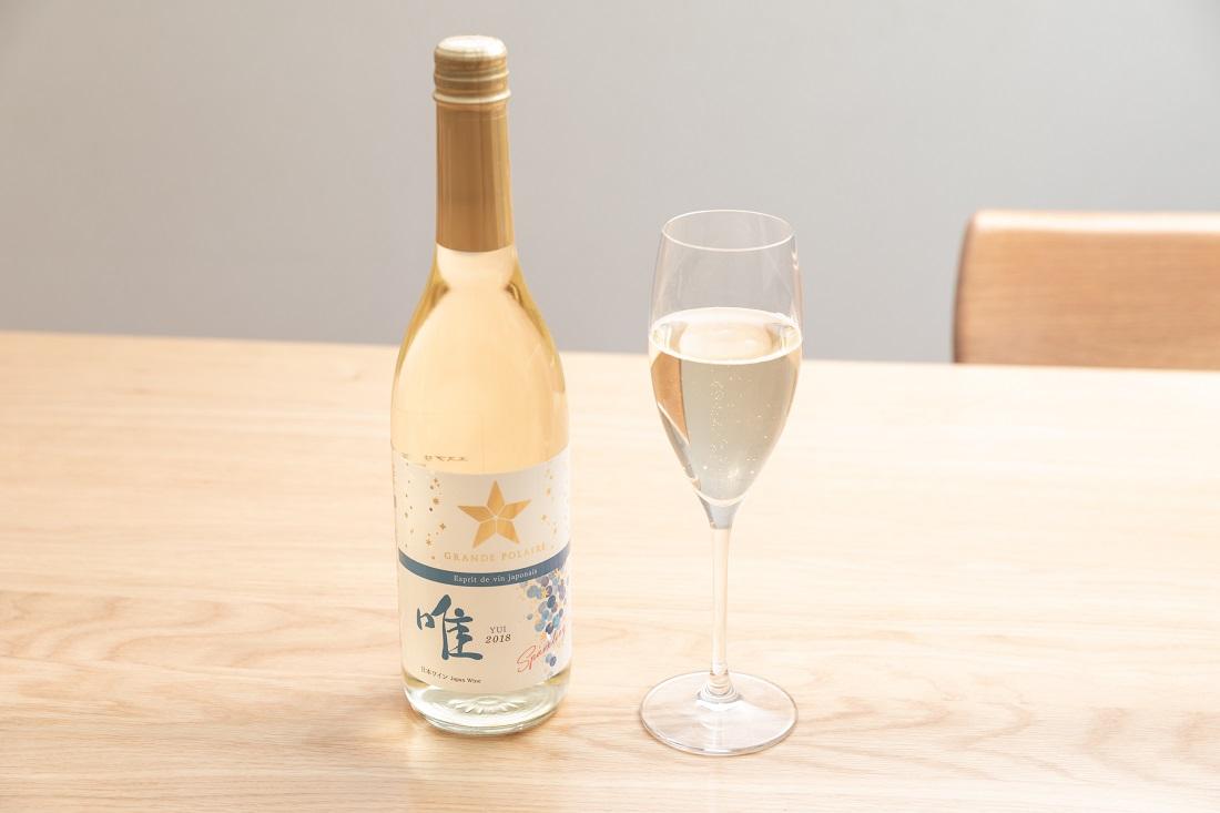 「グランポレール エスプリ ド ヴァン ジャポネ 唯 -YUI- スパークリング」ワインボトルとスパークリングワイン用グラスの置かれたテーブル