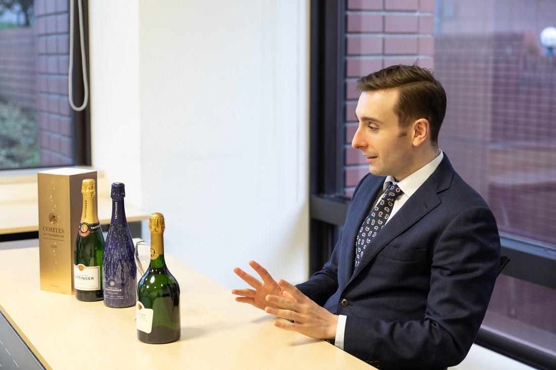 テタンジェのシャンパーニュボトルを前に話すテタンジェ・オフィシャル・アンバサダーのシュビヤー・クリストファー氏