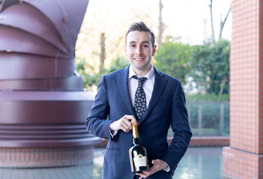 「コント・ド・シャンパーニュ ブラン・ド・ブラン 2008」のボトルを持って立つテタンジェ・オフィシャル・アンバサダーのシュビヤー・クリストファー氏
