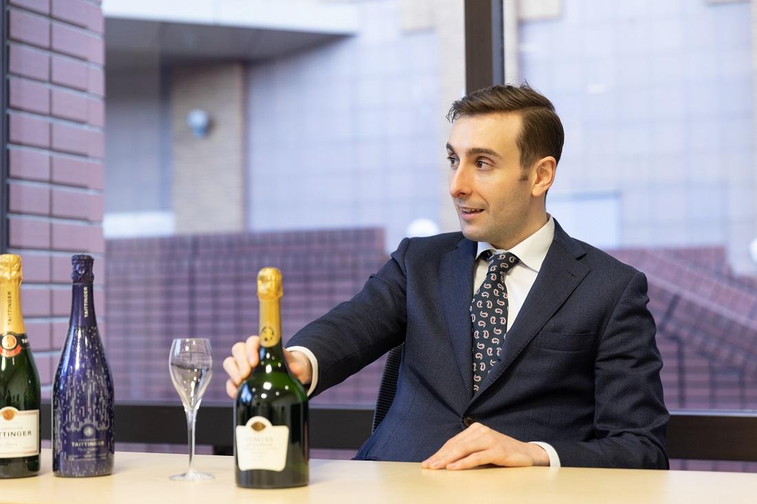 「コント・ド・シャンパーニュ ブラン・ド・ブラン 2008」のボトルに触れながらペアリングについて語るテタンジェ・オフィシャル・アンバサダーのシュビヤー・クリストファー氏