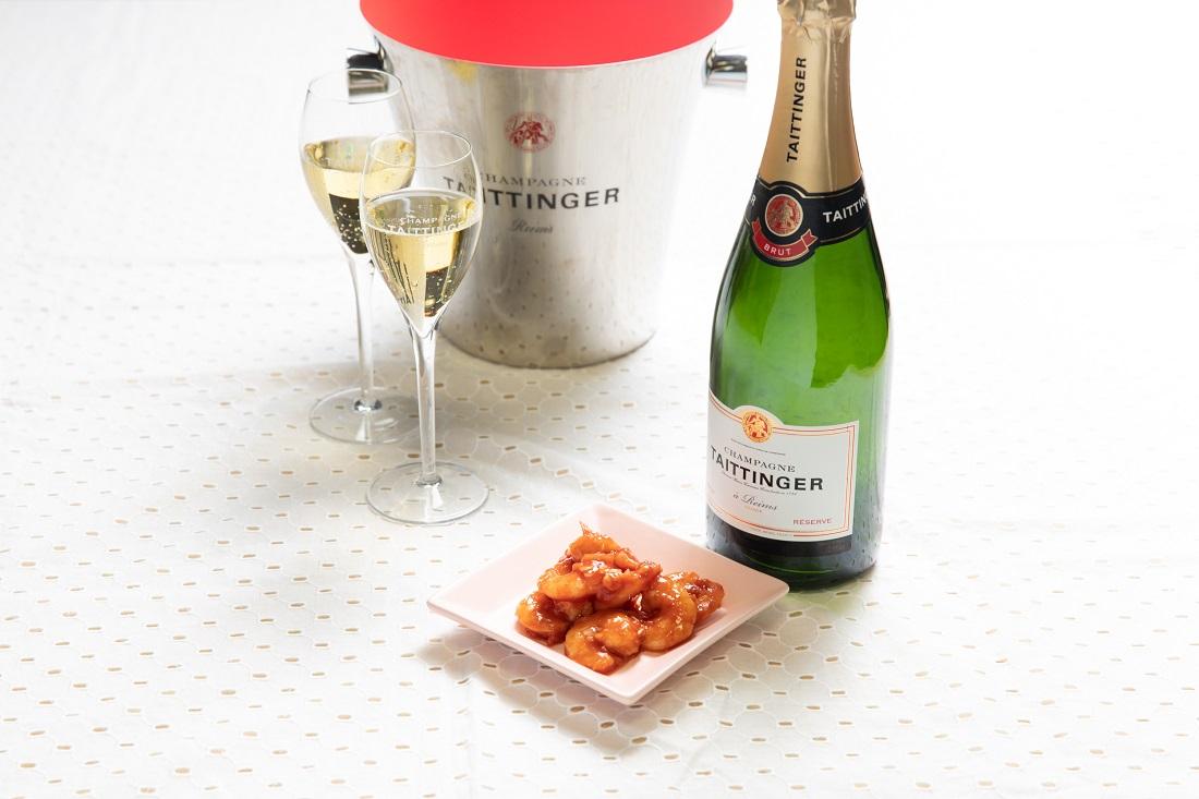 テタンジェ「ブリュット レゼルヴ」シャンパーニュボトルとシャンパーニュグラス、お皿に盛り付けた「エビチリ」