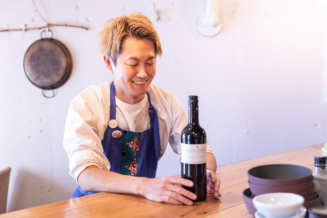 〈ヌヴィアナ・テンプラニーリョ・カベルネ・ソーヴィニヨン〉のワインボトルを前に笑顔の「エスタシオン」野堀貴則シェフ
